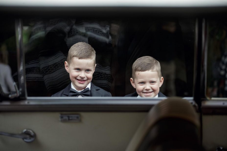 Two young page boys smiling framed by wedding car window