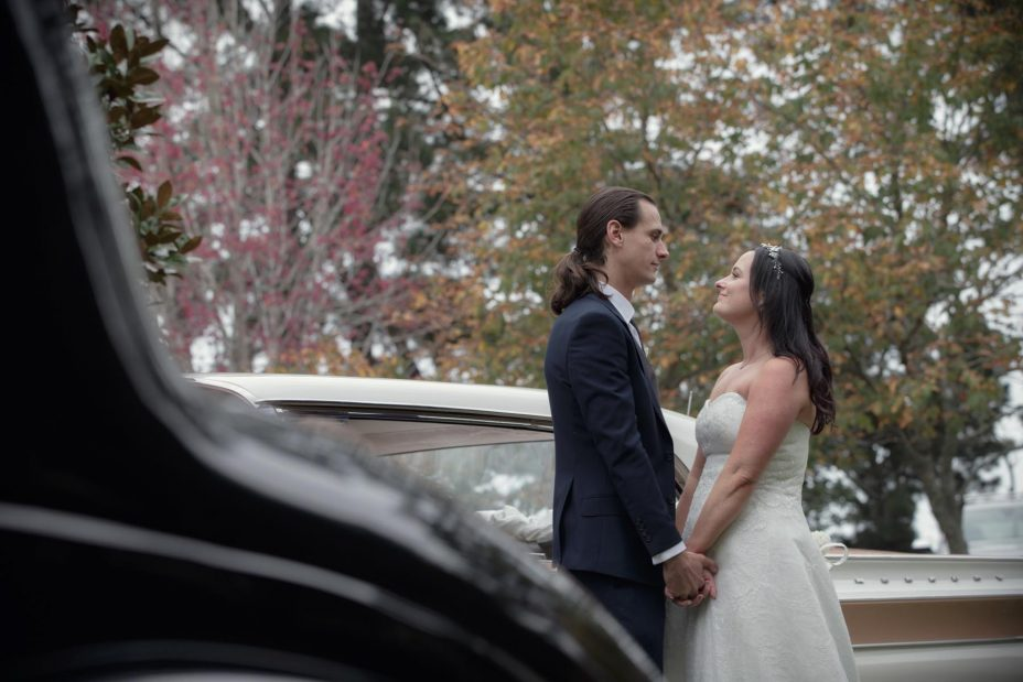 Bride and groom embrace next to their classic American wedding car