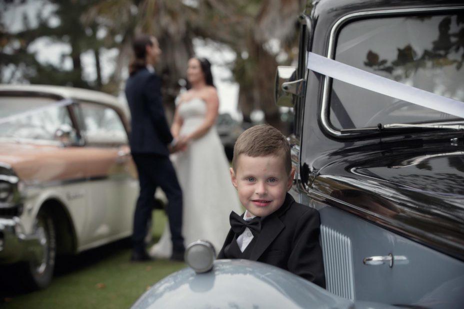 Cute pageboy leans on teh fender of classic wedding car