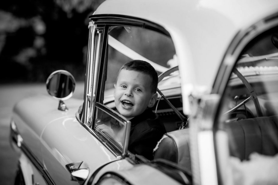 cute little boy wearing bow tie looks out of the window of Classic American car