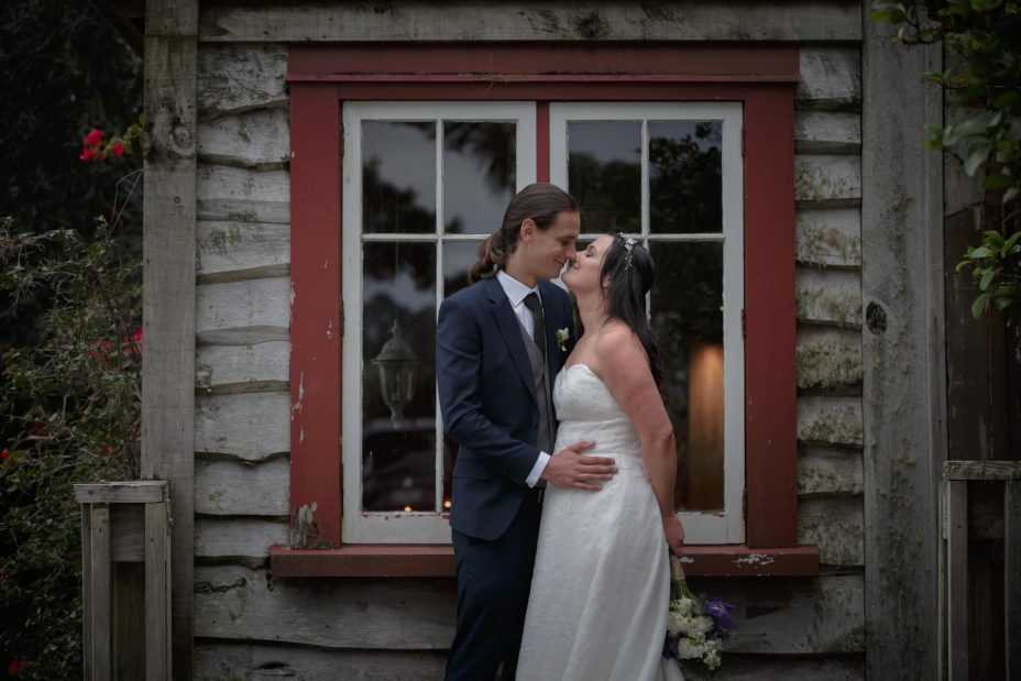 Bride and groom kiss infront of traditional wood window