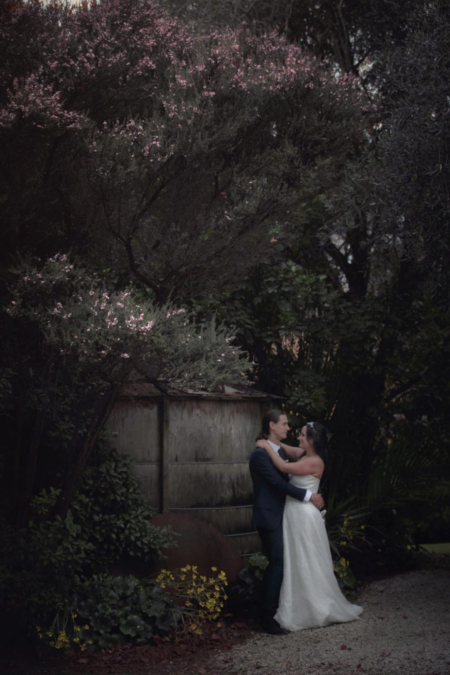 bride and groom embrace in the gardens at Kumeu Valley Estate