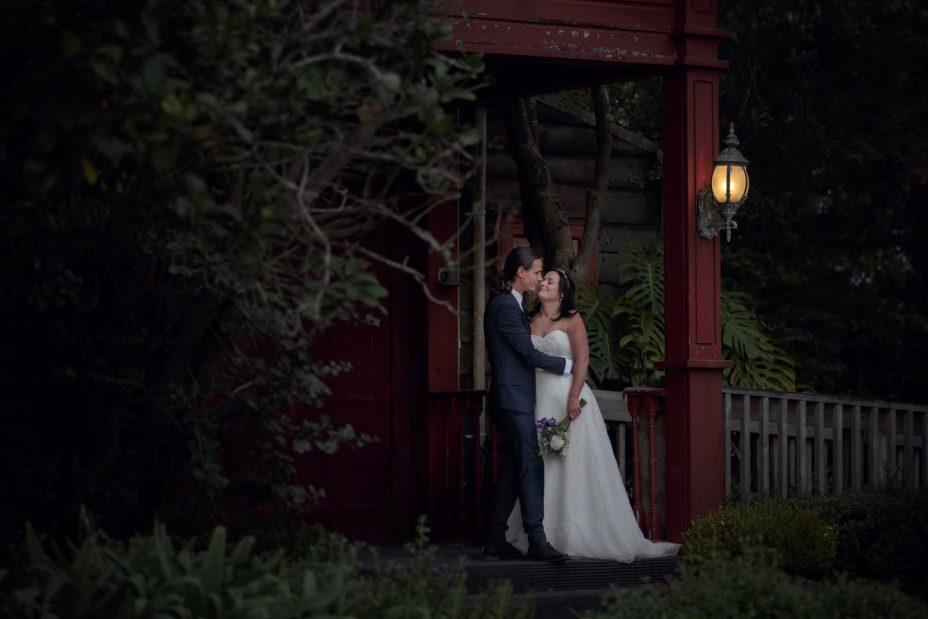 Bride and groom kiss at sunset on the front porch of Kumeu Valley Estate