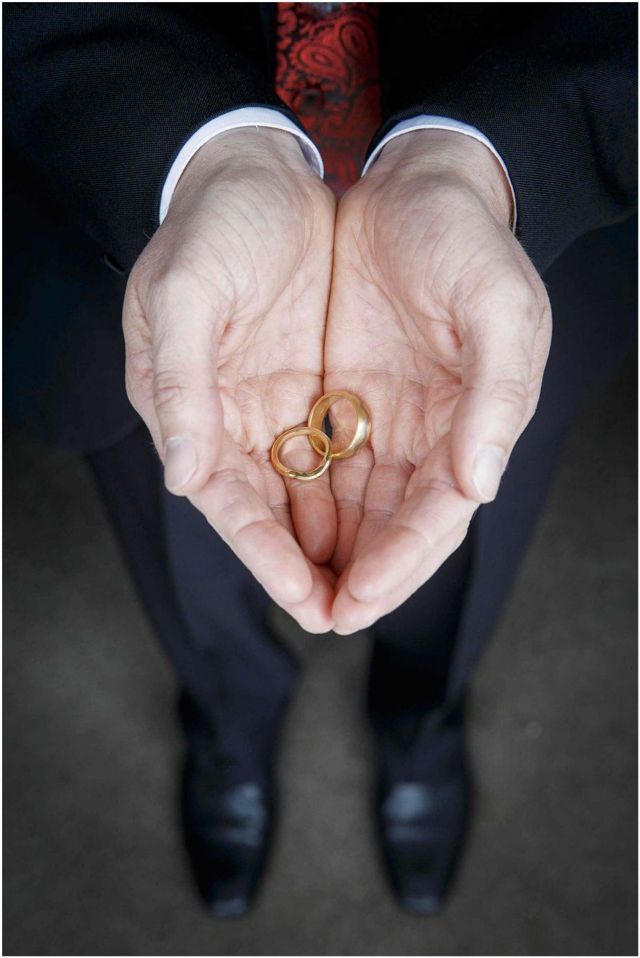 Close up photo of gold wdding rings in a man's cupped hands.