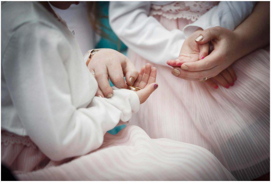 Bridesmaids holding a gold wedding ring