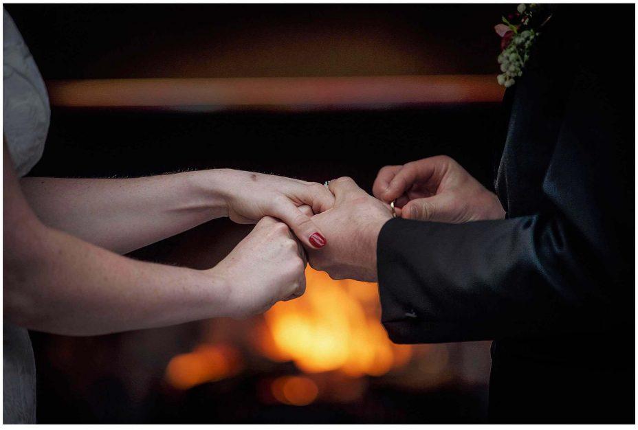 Groom places wedding ring on ring finger during wedding ceremony at Mantells Mount Eden.v