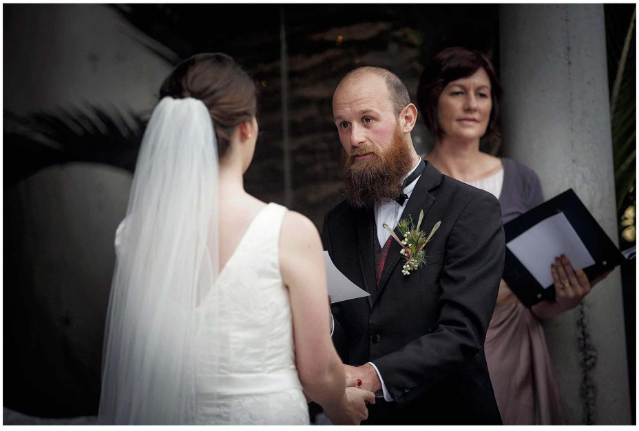 Bride and groom look into each other's eyes and smile during their wedding ceremony at Mantells Mount Eden.