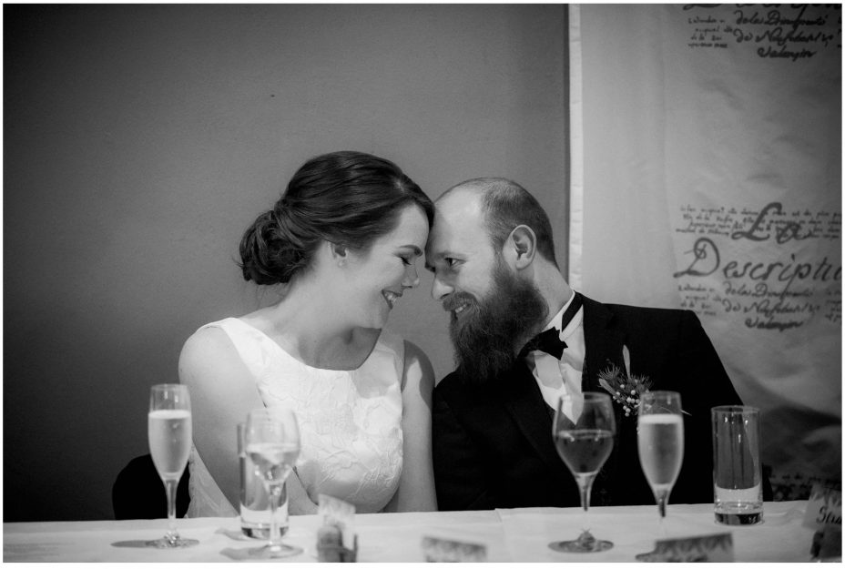 Bride and groom touch foreheads and smile as they listen to the speeches at their wedding reception at Mantells in Mount Eden.