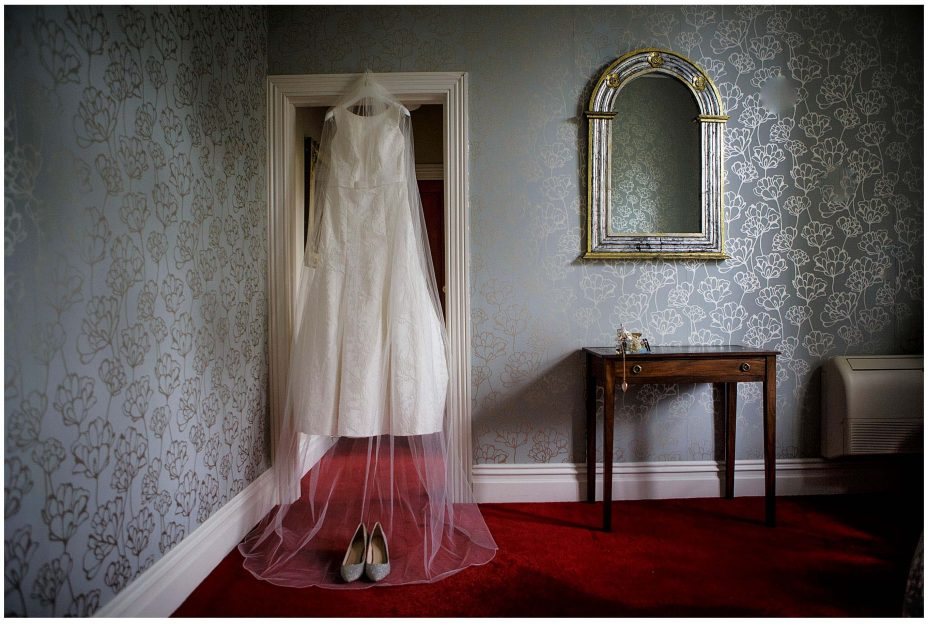 Classical white wedding dress and veil hanging from the door frame alongside an antique mirror at Mount Eden Villa.