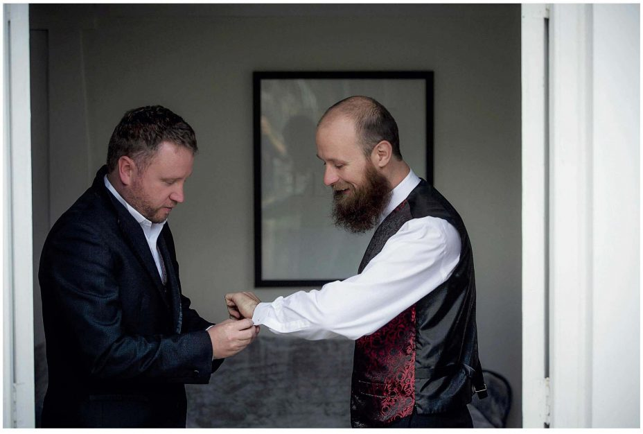 Best man helps wedding day groom put on some silver cuff-links.