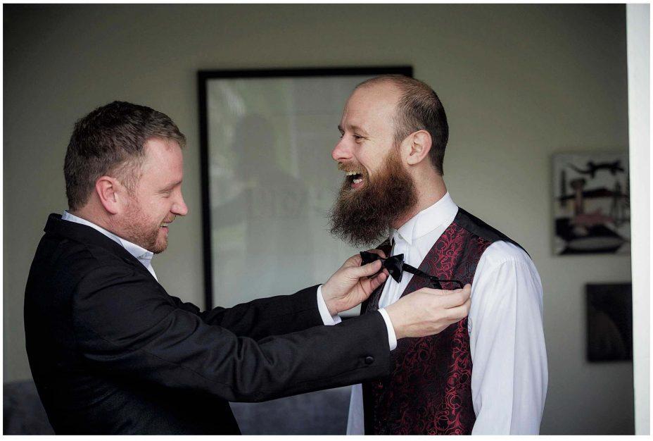 Best man helps wedding day groom to tie a proper bow tie.