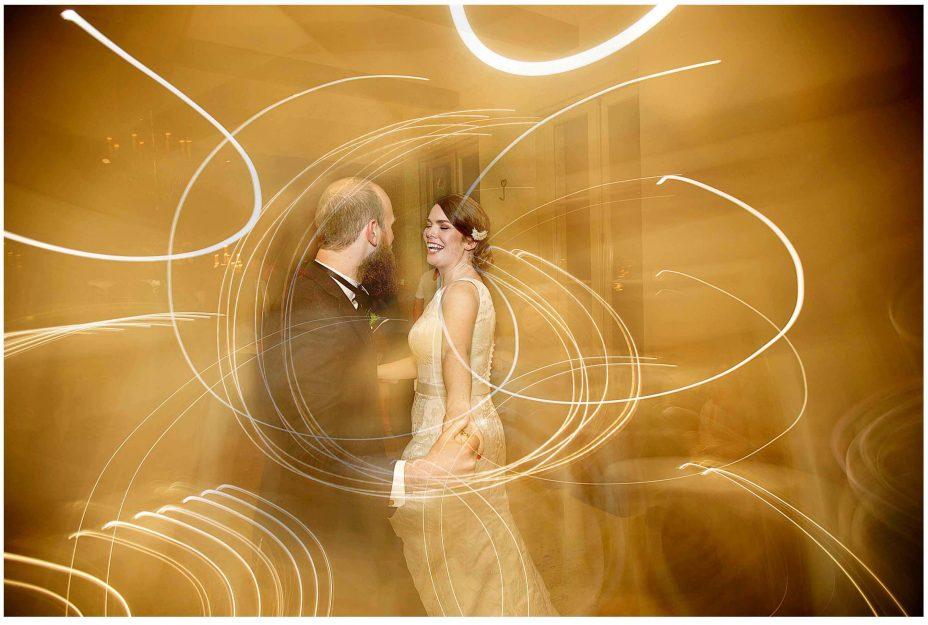 Bride and groom share their first wedding dance in a blaze of golden light. Mantells Mount Eden.