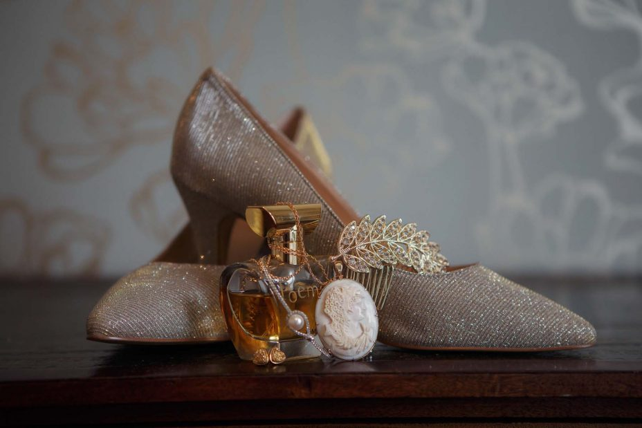 Sparkling gold Wedding shoes. On an antique wooden table top with bride's perfume and jewellery in a bedroom at Mount Eden Villa.