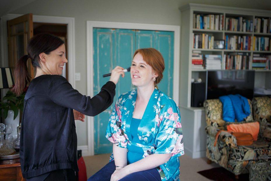 Bridesmaid wearing light blue floral kimono robe has her wedding make up applied at Mount Eden Villa.