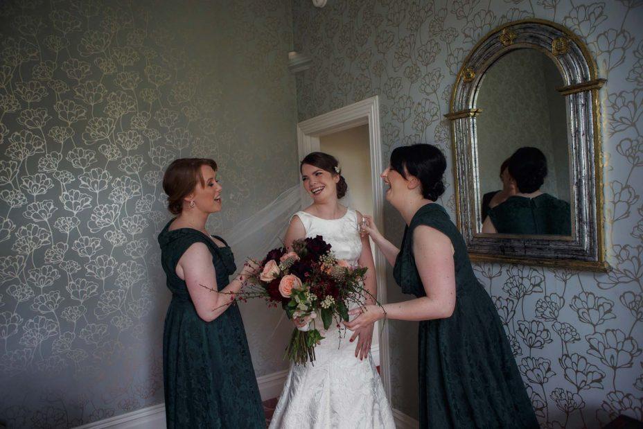 Bridesmaids spray perfume for the bride in a bedroom at Mount Eden Villa as she prepares for her wedding