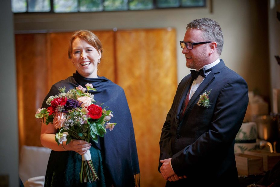 Bridesmaid holding flower bouquet laughs with a groomsman in formal black suit.