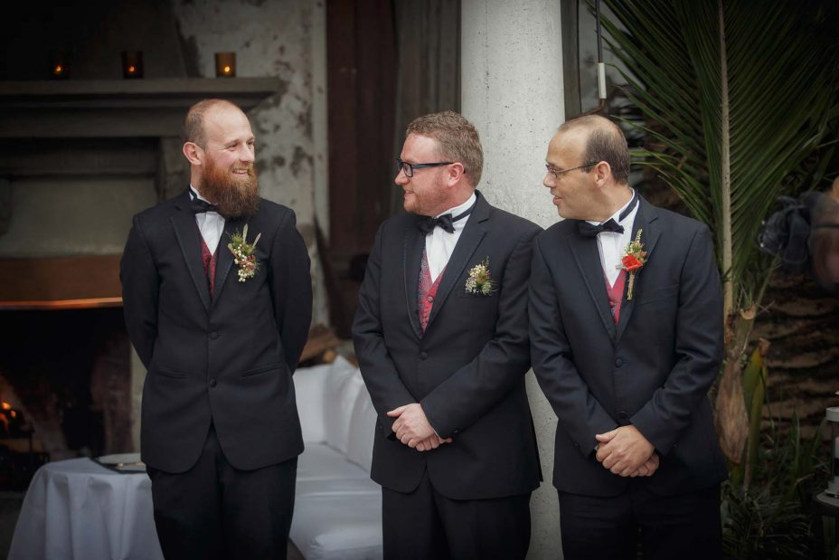 The groom and groomsmen wearing formal black suits and bow ties smile and chat together in front of the fireplace as they await the bride.