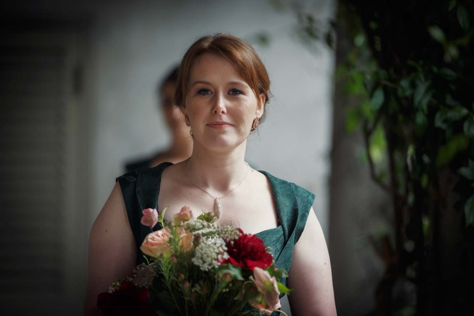 Bridesmaid looks directly into the camera as she walks towards the wedding ceremony at Mantells in Mount Eden.