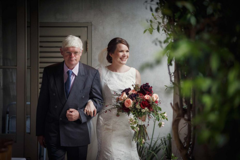 Bride and her father walk arm in arm down the isle towards her wedding ceremony at Mantells Mount Eden.
