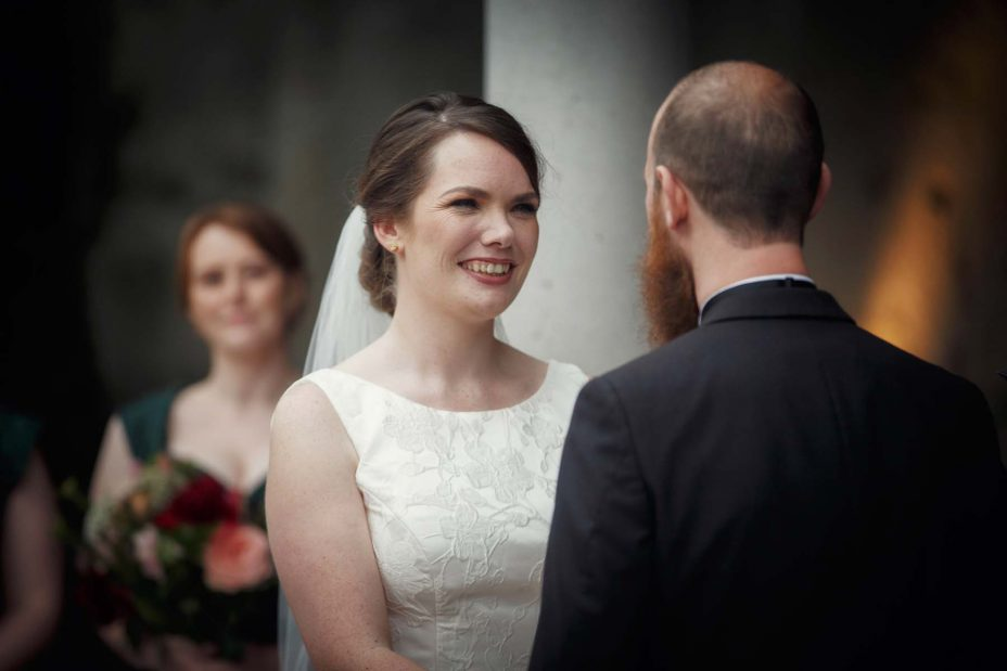 Smiling happy bride looks into the grooms eye's during their wedding ceremony .