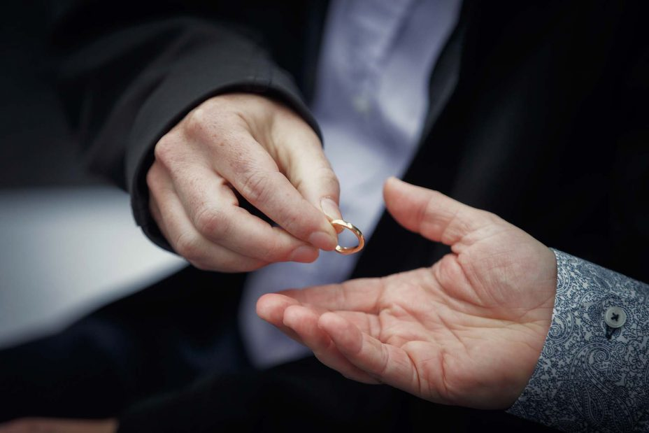 Bride's gold wedding ring is passed from hand to hand for all the wedding guests to hold at a ceremony at Mantells in Mount Eden.