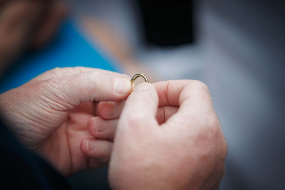 Close up photo of one of the guests holding the bride's gold wedding ring.