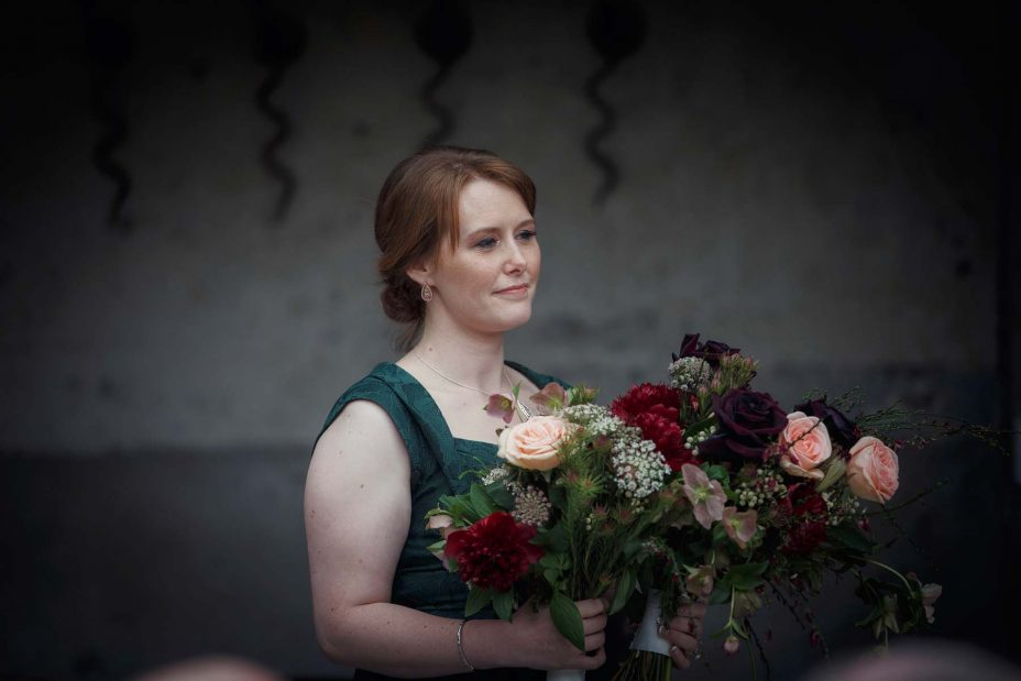 Bridesmaid holds the bride's wedding flowers during the ceremony at Mantells in Mount Eden.