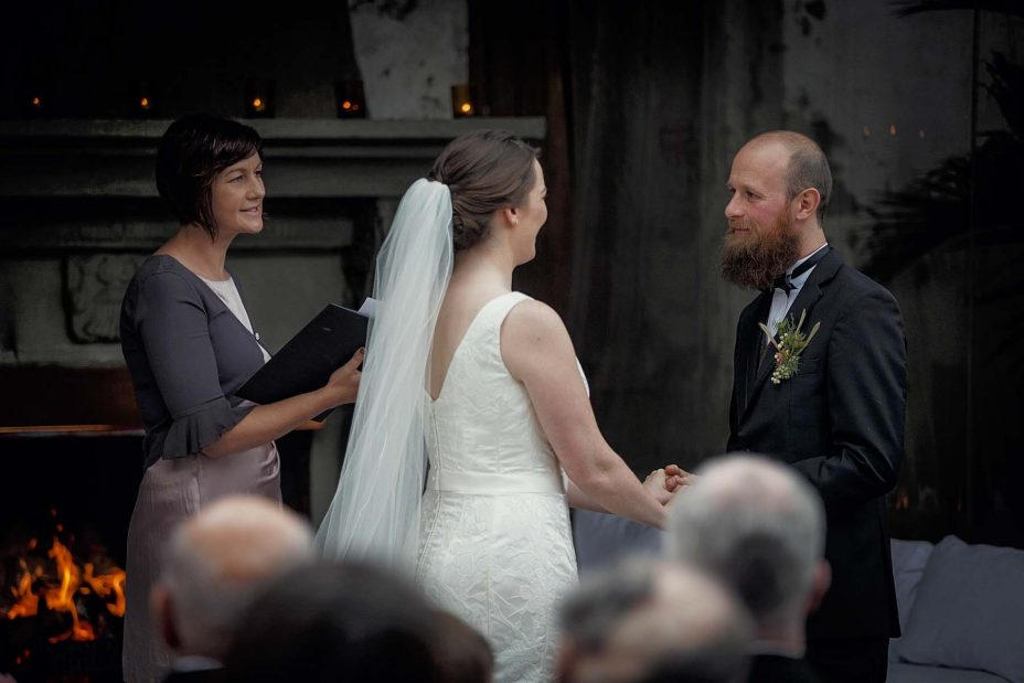 Bride and groom look into each other's eyes and smile during their wedding ceremony at Mantells Mount Eden.v