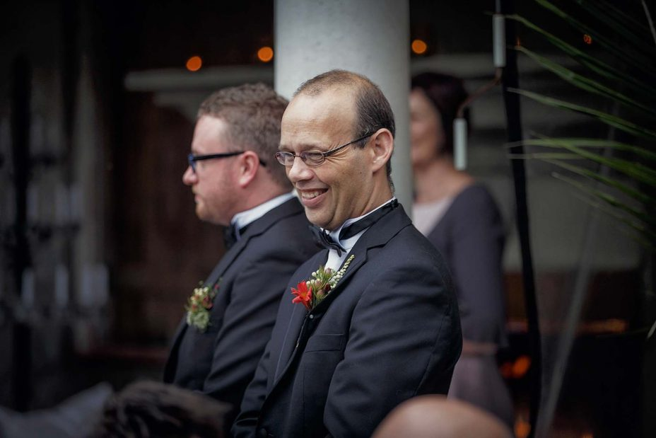 Groomsman wearing formal black bow tie and buttonhole flower smiles broadly at wedding guests.