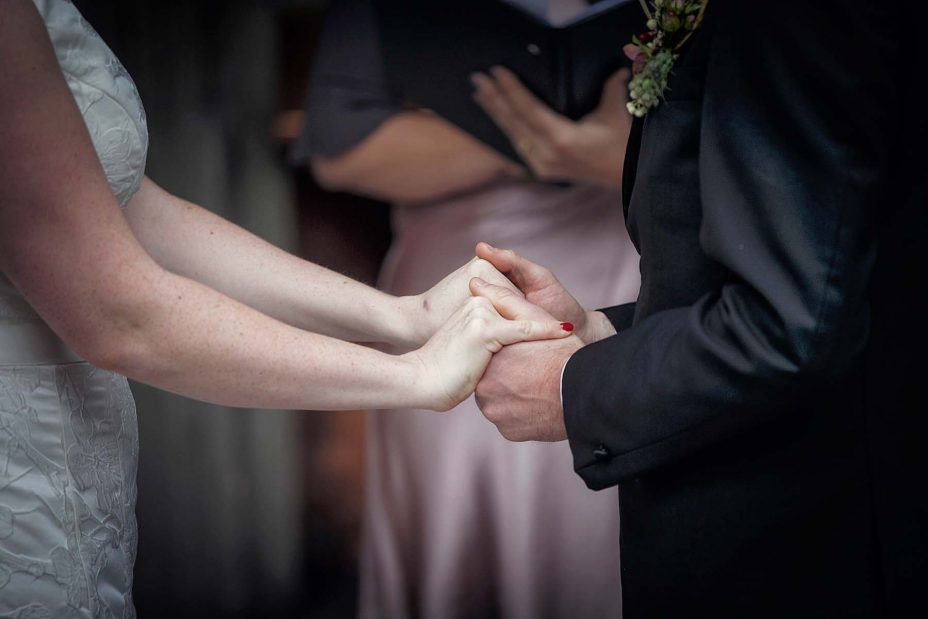 Close up photo of bride and groom hold hands during their wedding ceremony at Mantells Mount Eden.