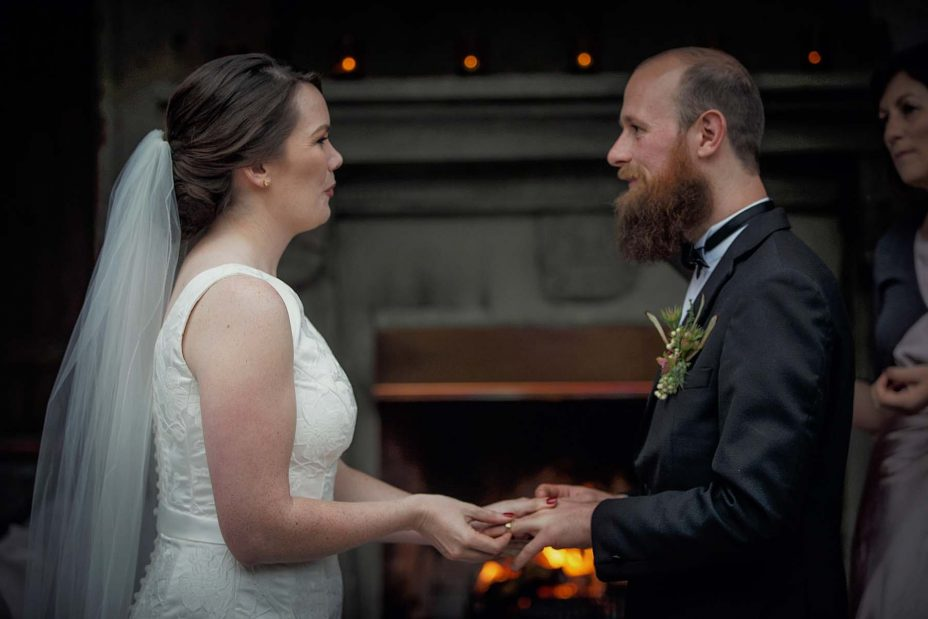 Bride pushes gold wedding ring into her groom's finger during their wedding ceremony in front of the fireplace at Mantells in Mount Eden.