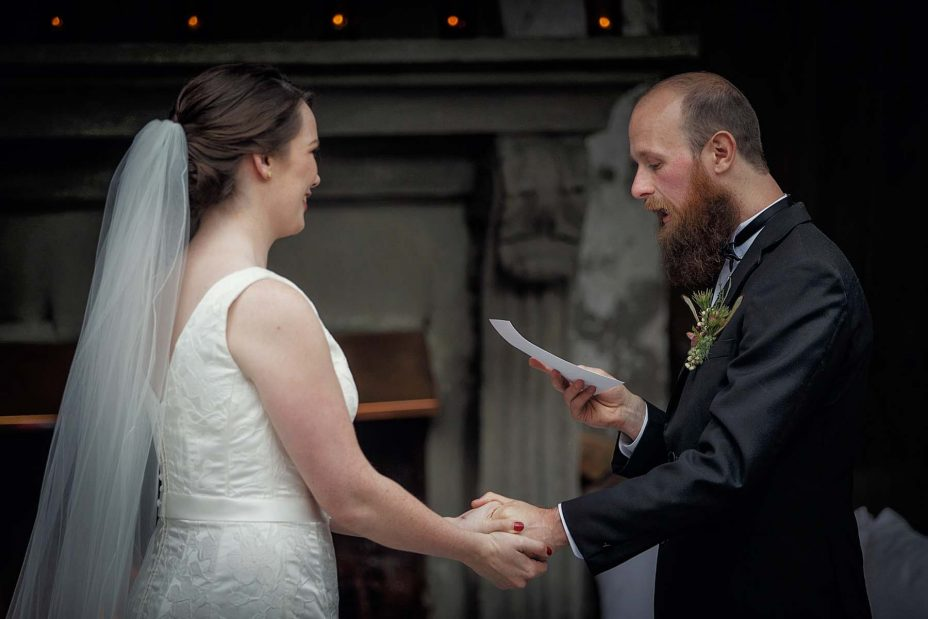 Smiling, happy bride and groom hold hands whilst groom reads his wedding vows in front of the fireplace at Mantells in Mount Eden.