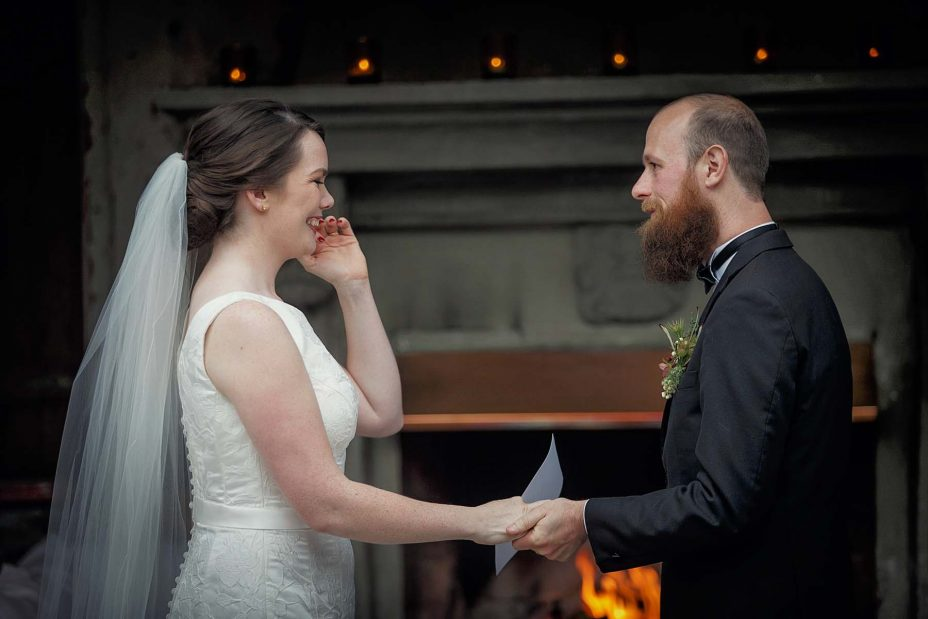 Smiling, happy bride and groom hold hands in front of the fireplace at Mantells in Mount Eden.