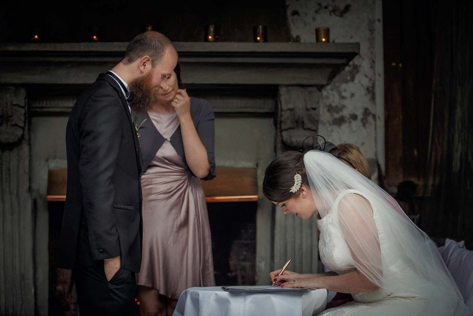 he bride sits and completes the wedding register following the ceremony at Mantells in Mount Eden.