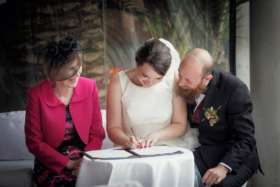Bride and groom sit and complete their wedding register following their ceremony at Mantells in Mount Eden.