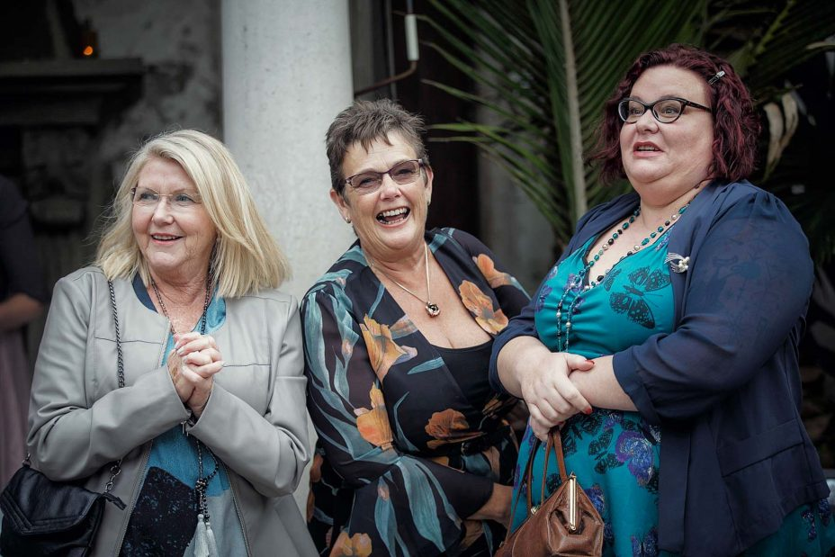 Wedding guests laugh together after the wedding ceremony in front of the fireplace at Mantells in Mount Eden.