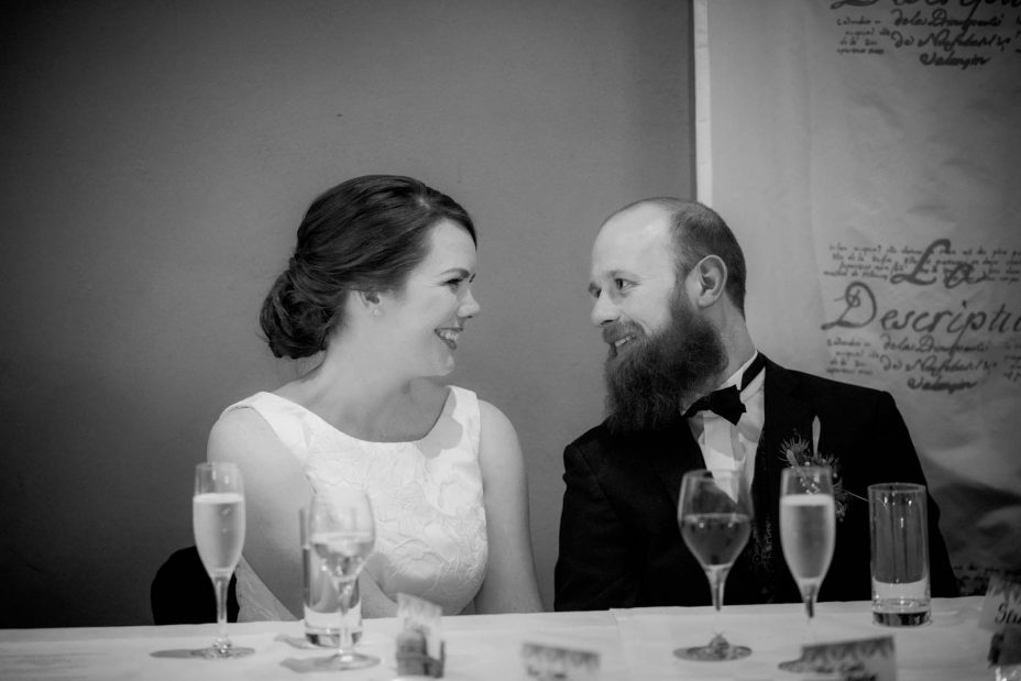 A loving moment captured as bride and groom gaze into each other's eyes and smile whilst they listen to the speeches at their wedding reception at Mantells in Mount Eden.