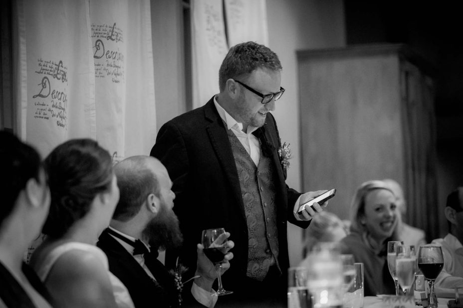 best man reads his speech from his mobile phone during a wedding reception at Mount eden Villa.