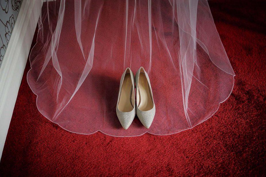 Bride's wedding shoes framed by her viel on a red carpet at Mount Eden Villa.