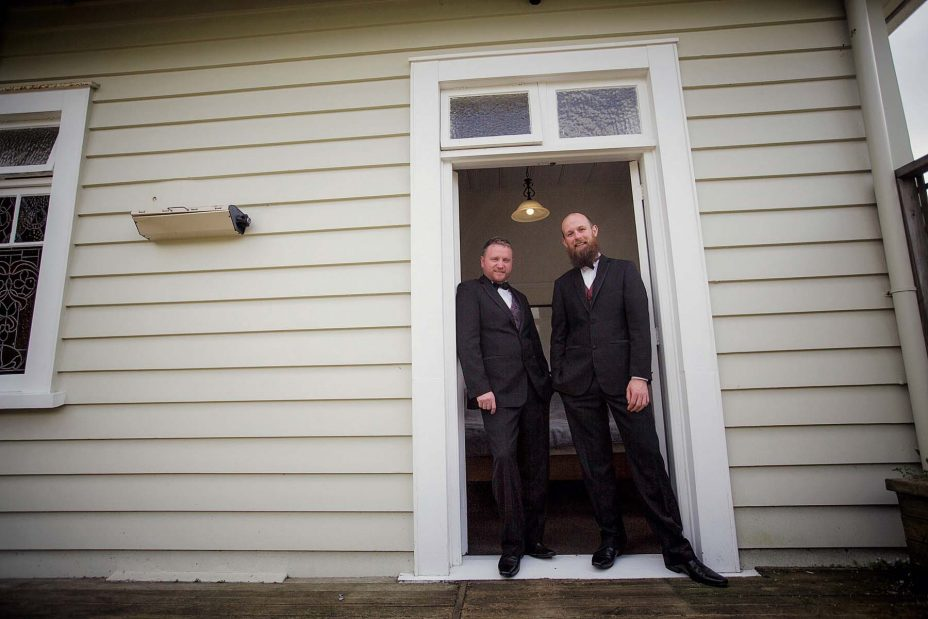 Wedding day groom helps his best man stand in the doorway of an old weatherboard villa as they prepare for the wedding ceremony at Mantells in Mount Eden.