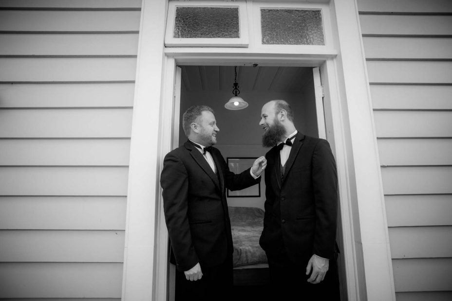 Wedding day groom helps his best man stand in the doorway of an old weatherboard villa as they prepare for the wedding ceremony at Mantells in Mount Eden.Black and white photo.