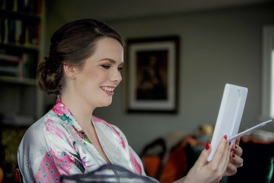Wedding day floral kimono robe looks at herself in a small mirror as she has her wedding make up applied at Mount Eden Villa.
