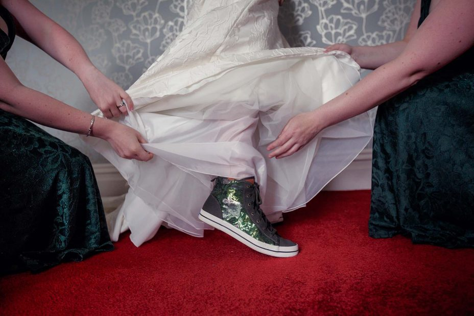 Bridesmaids lift the bottom of the bride's classical white wedding dress to reveal her unusual sparkling green wedding boots.