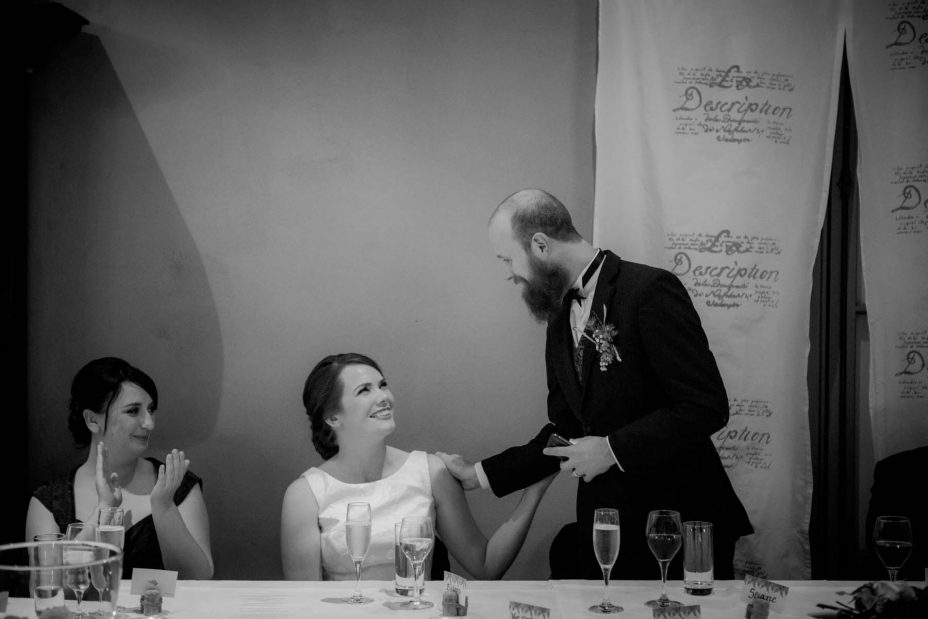 Bride and groom touch each other whilst gazing into each other's eyes as groom makes his speech during their wedding reception at Mantells in Mount Eden.