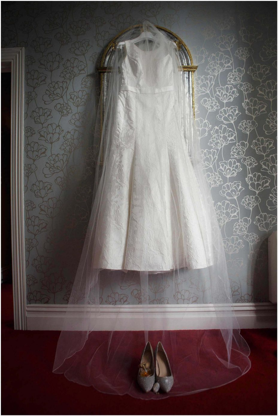 Classical white wedding dress and veil hanging from antique mirror at Mount Eden Villa.