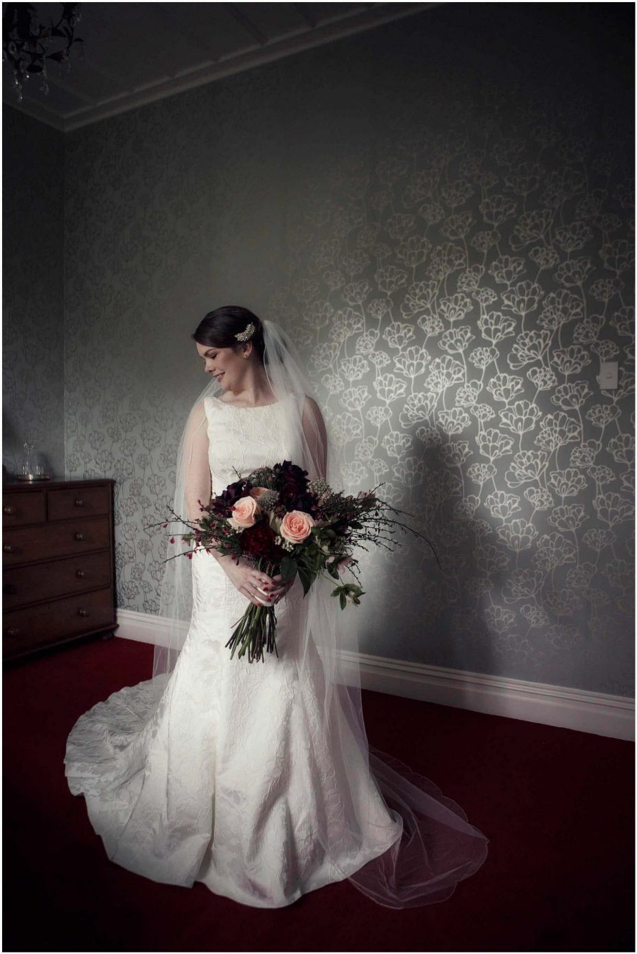 Bide wearing classical white wedding dress with train holding floral bouquet at Mount Eden Villa