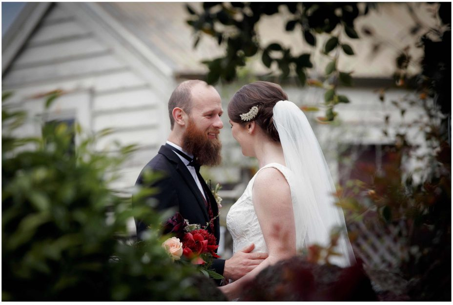 Wedding day groom smiles happily as his bride to be as she reveals herself in her wedding dress for the first time in the garden at Mount Eden Villa.