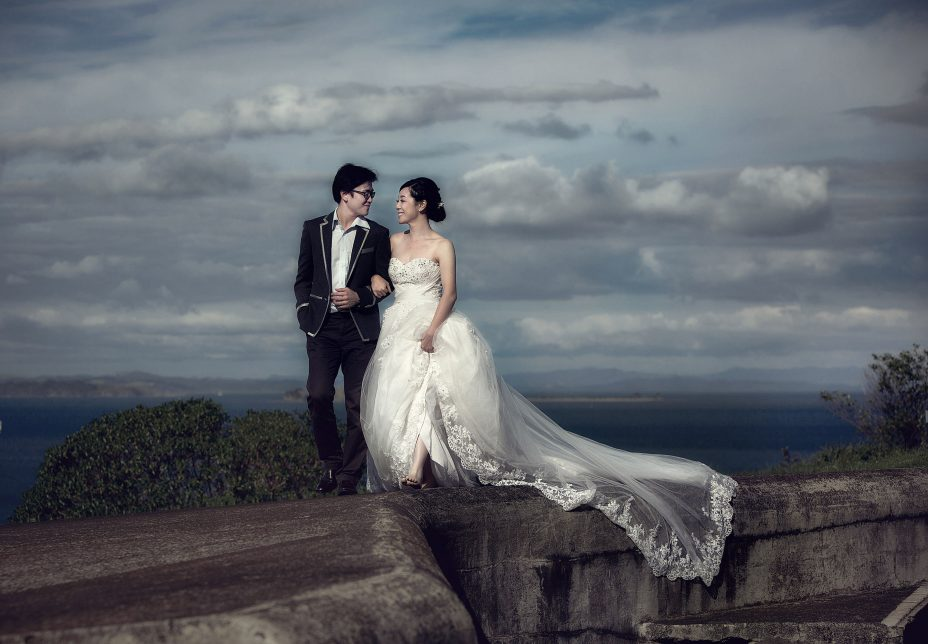 Chinese newlyweds walk arm in arm at North Head in Auckland. in the dramatic afternoon light. The bride wearing a full lenght white wedding dress with long gausey train trailing behind her. The couple share a special moment together captured by Auckland Wedding photographer Chris Loufte.