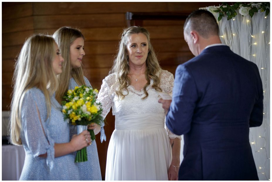 Bride looks lovingly at groom reading poem in wedding ceremony at Puhoi Village Hall