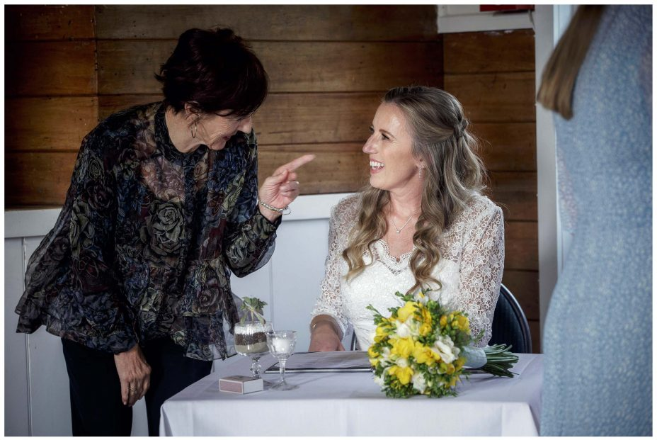 Bride jokes with marriage celebrant as she signs wedding register